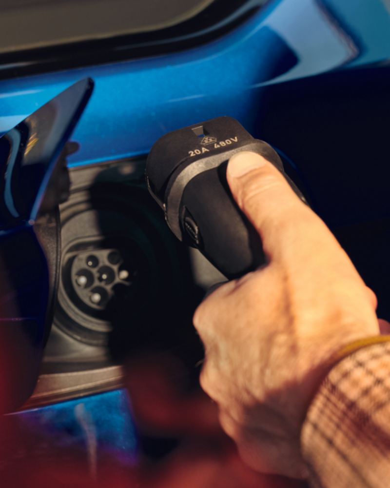 Primer plano de una mano conectando un cargador eléctrico a un Volkswagen Touareg R