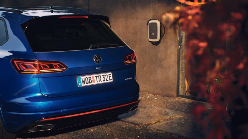 Vista de la parte trasera de un Volkswagen Touareg R aparcado junto a un Wallbox