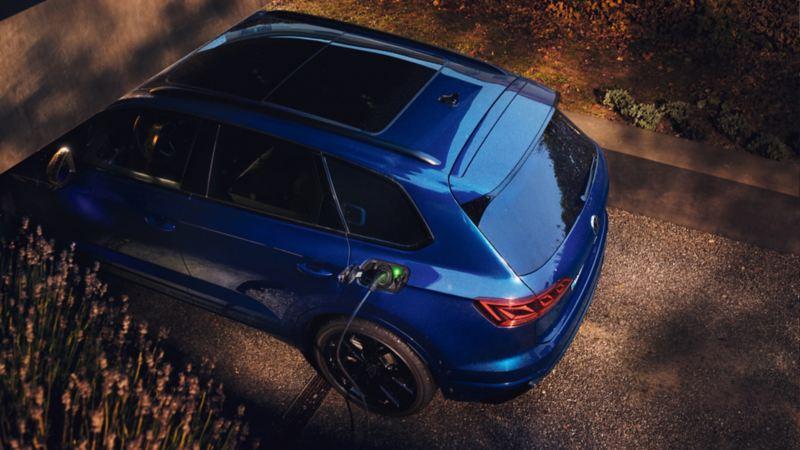 Vista desde arriba de un Volkswagen Touareg R azul conectado a un cargador eléctrico