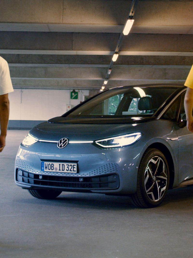 Två män går mot en Volkswagen ID.3