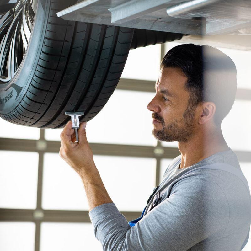 Ein VW Servicemitarbeiter misst die Reifenprofiltiefe eines VW Fahrzeugs