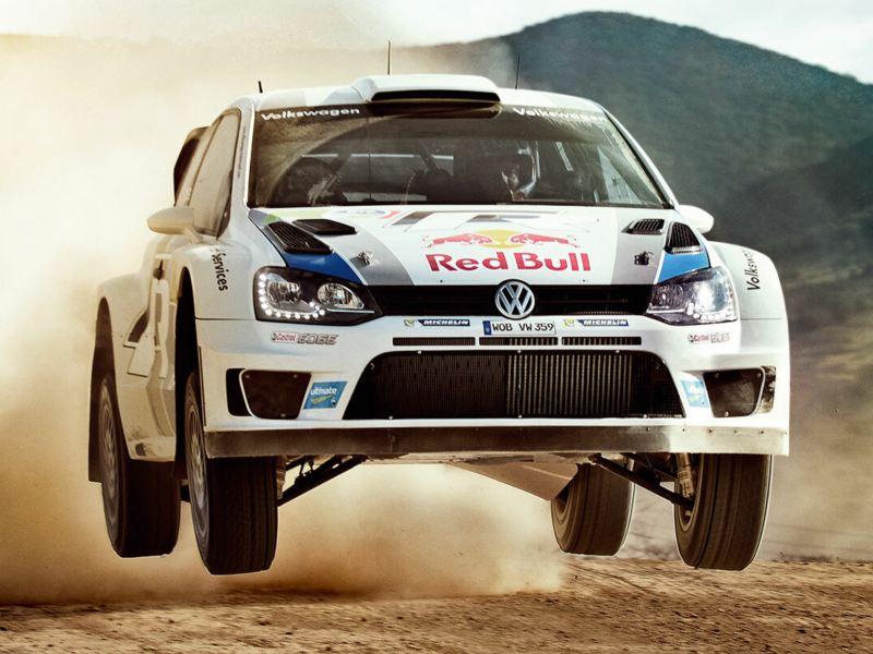 Frontansicht eines fahrenden Racing-Beetles auf einer Sand-Rennstrecke im Sprung