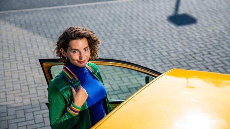Frau steht bei geöffneter Tür vom Auto.