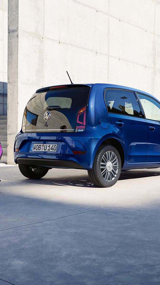 Woman sitting on camping chair infront of VW up! UNITED