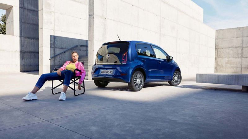 Frau sitzt auf Campingstuhl vor VW up! UNITED