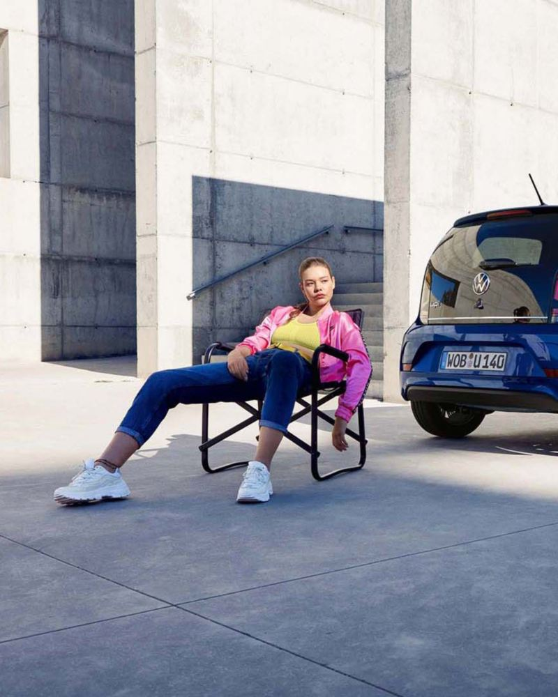 VW e-up! UNITED Heckansicht, Frau sitzt in Camping-Stuhl daneben.