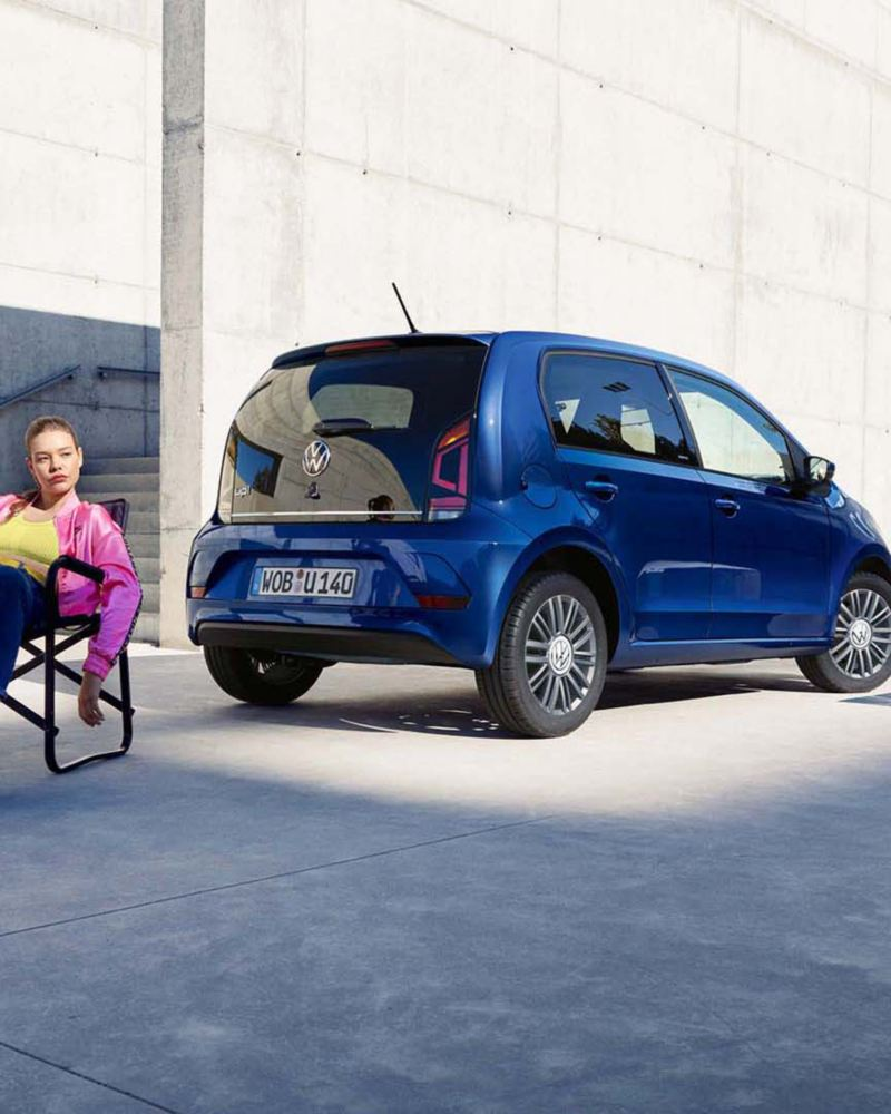Woman sitting on camping chair in front of VW up! UNITED