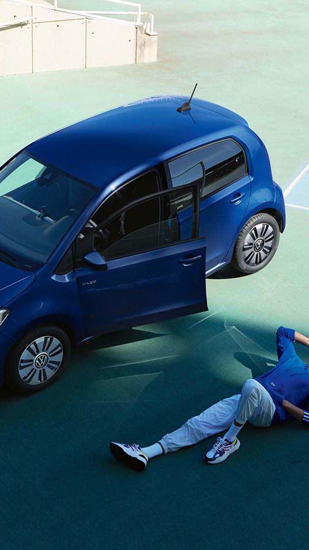 Mann liegt vor VW e-up! UNITED mit geöffneter Fahrertür auf Tartanbahn