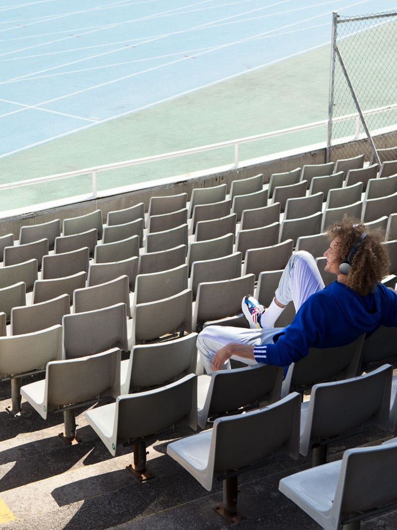 Man in stadium, sitting alone, listening to music