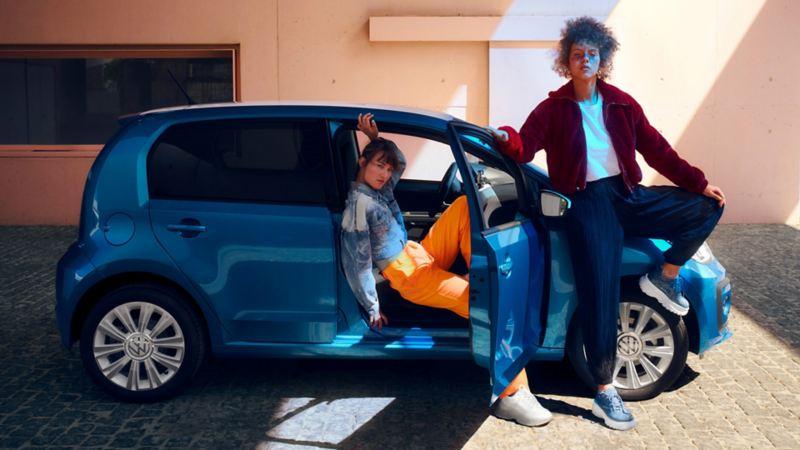 Ragazza appoggiata e ragazza seduta sul sedile anteriore passeggero di Nuova up! Volkswagen city car