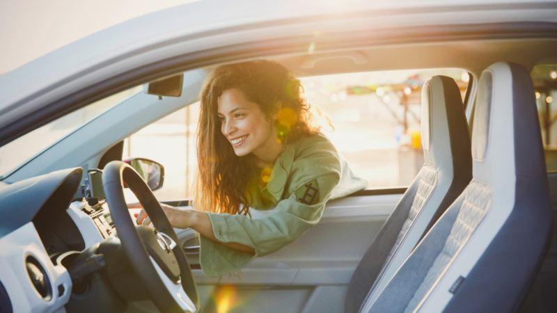 Frau lehnt sich durch Fahrzeugfenster – Kilometerleasing