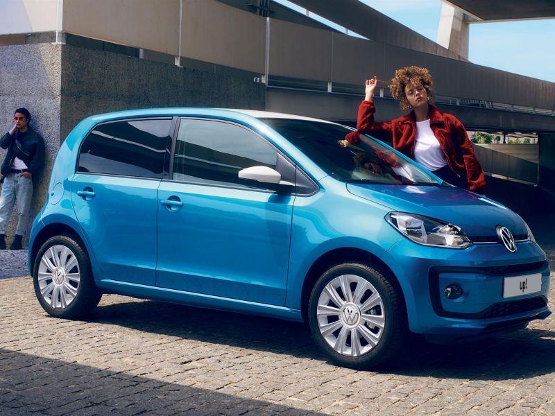 Ragazza appoggiata su Nuova up! Volkswagen parcheggiata su una strada acciottolata