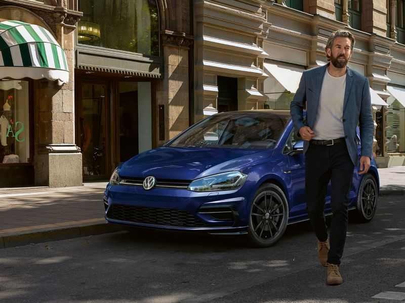 Man walking on street in front of a Golf R