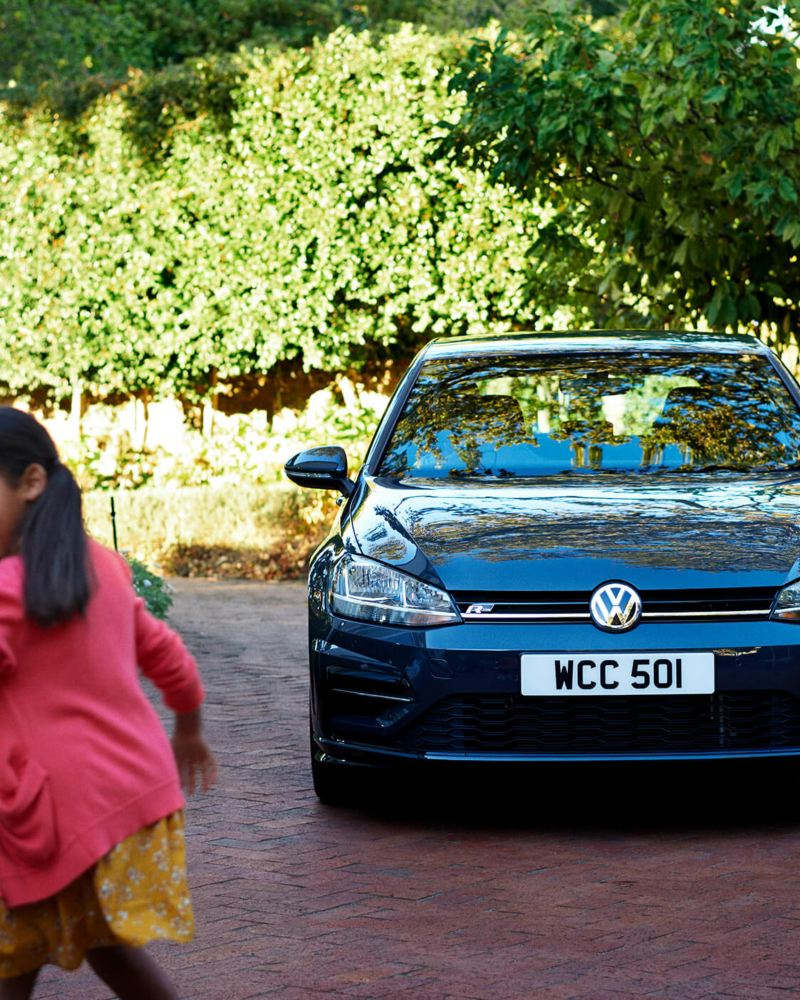 A Volkswagen car in a drive way with a girl playing in front of it