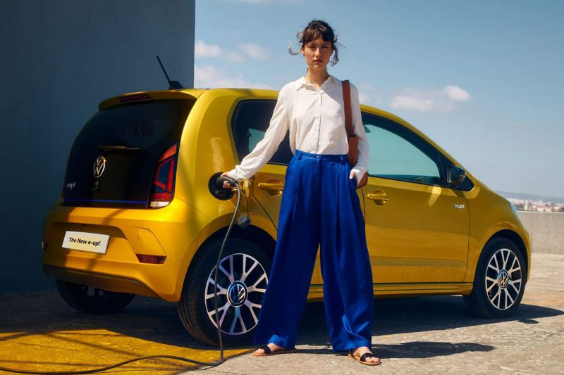 Exterior shot of woman charging a Volkswagen e-up!