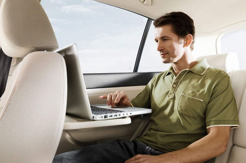 A man using his laptop on a foldout table in the back passenger seat of a Volkswagen Golf.