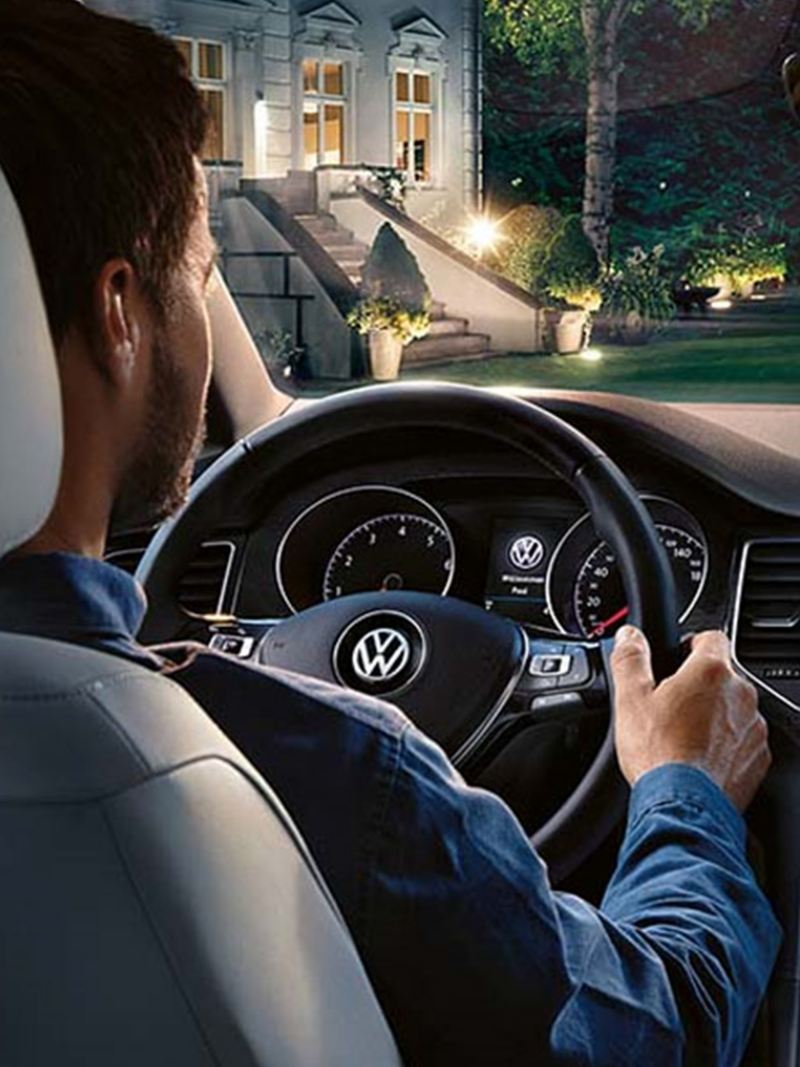 A man driving a Volkswagen Golf SV, on a well lit suburban street.