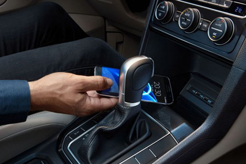 Person placing their phone in the dashboard compartment of a Volkswagen Golf.