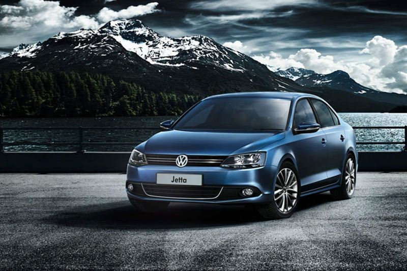 A blue Volkswagen Jetta surrounded by snow covered mountains.
