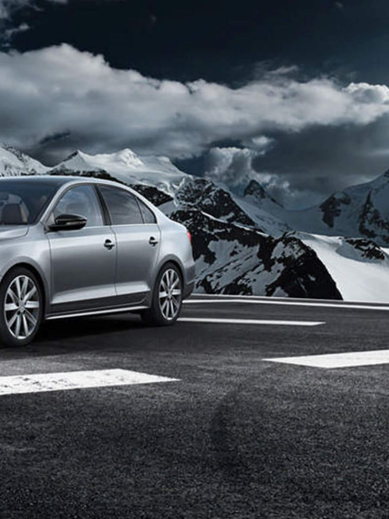 A silver Volkswagen Jetta, on a race track, surrounded by snow covered mountains.