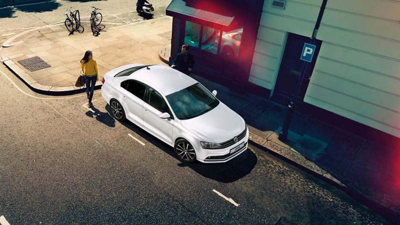 Ariel shot of a white Volkswagen Jetta, with a lady approaching.