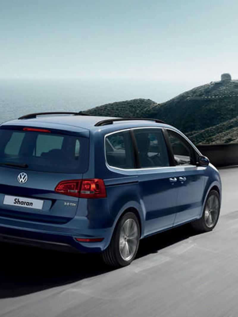 Blue Volkswagen Sharan, driving on a mountainous costal road.