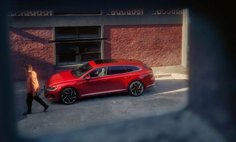 A side view of a red Arteon Shooting Brake on the street, from a window.