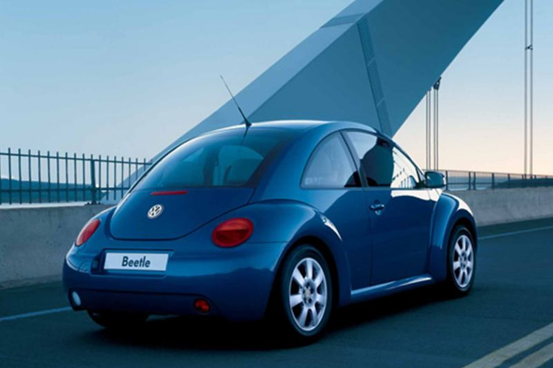 Rear view of a blue Volkswagen Bettle, crossing a suspension bridge.