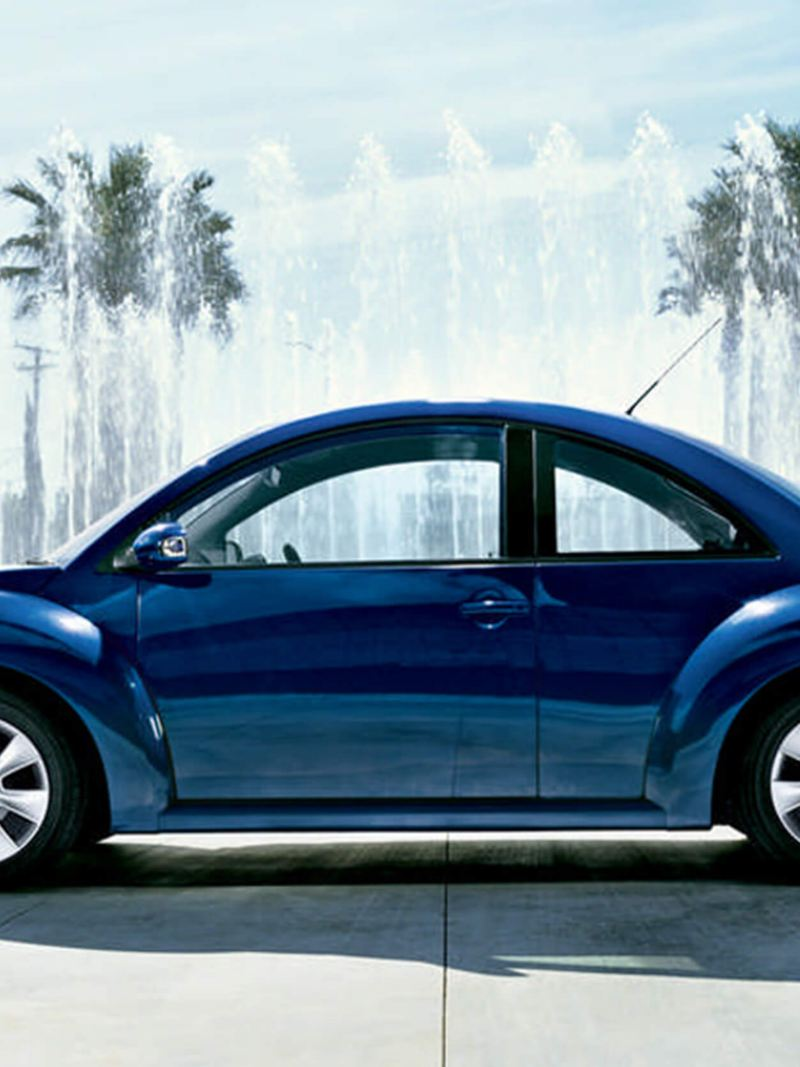 Profile shot of a blue Volkswagen Beetle, fountains and tree's in the background.