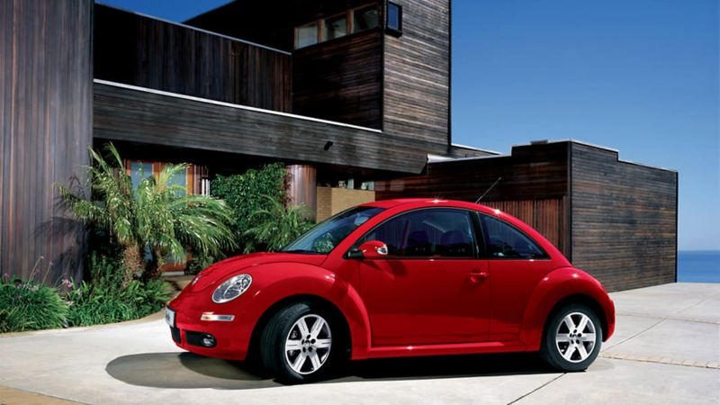 A red Volkswagen Beetle, outside a wooden-clad building, on a coastline.