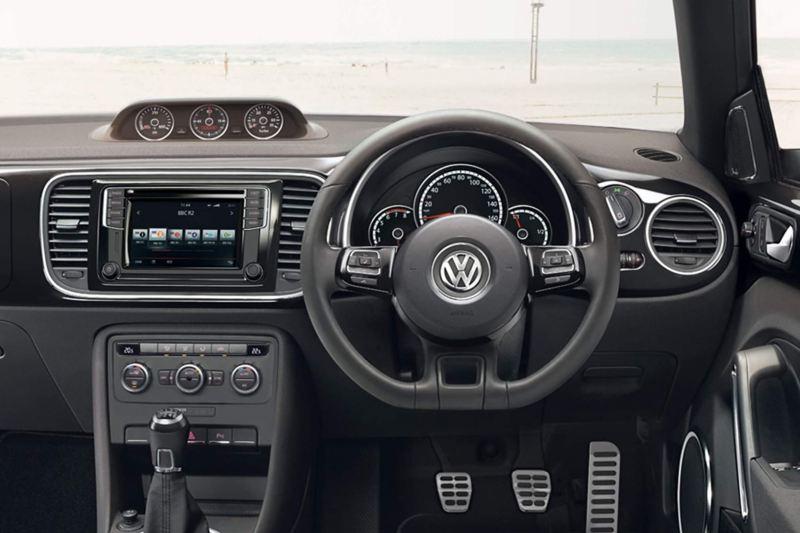Interior shot of the Volkswagen Beetle dash board and steering wheel.
