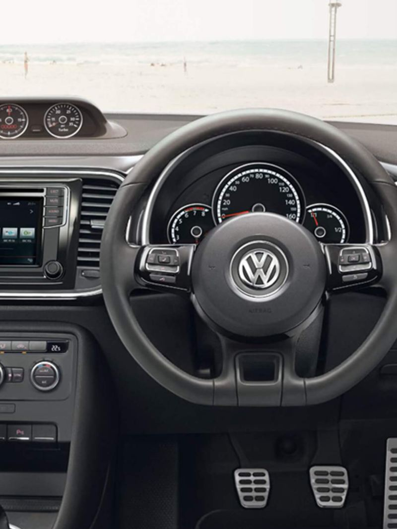 Interior dashboard and steering wheel shot of a Volkswagen Beetle Cabriolet.
