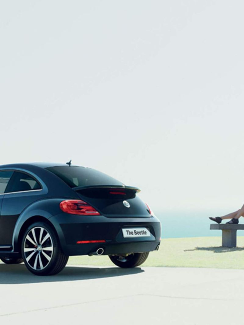 Rear shot of a black Volkswagen Beetle, a lady lay on a bench holding a balloon in the background.