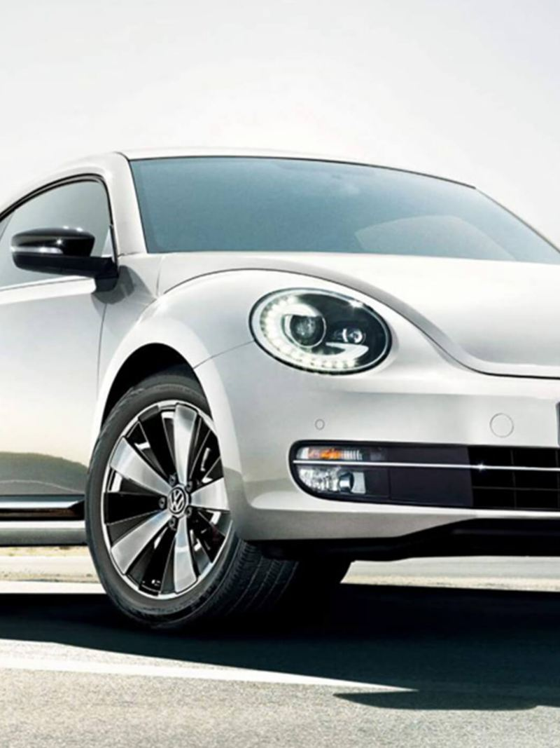 Front view of a white Volkswagen Beetle, on a desert. road