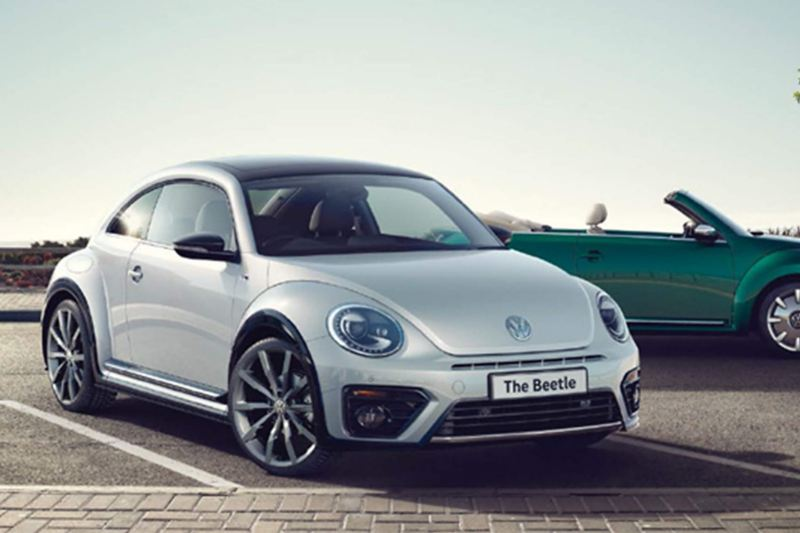 3/4 front view of a white Volkswagen Beetle, with a green Volkswagen Beetle Cabriolet in the background.