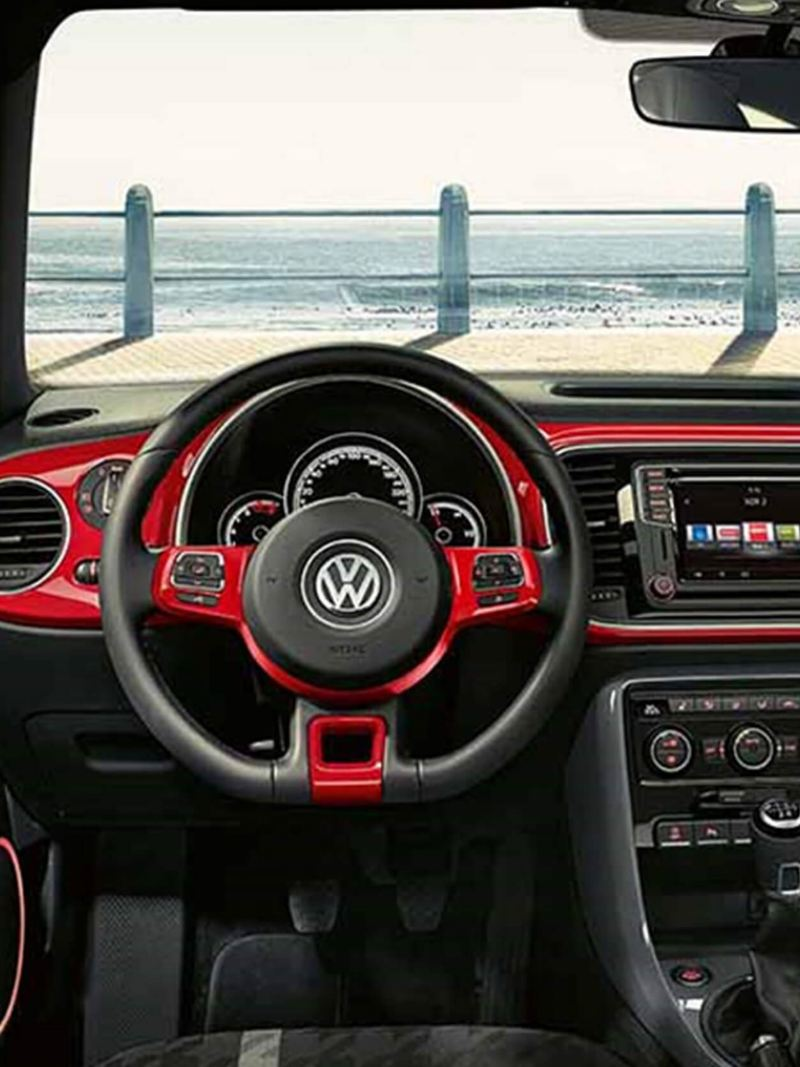 Interior dashboard shot of a Volkswagen Beetle, the see visible through the windscreen.