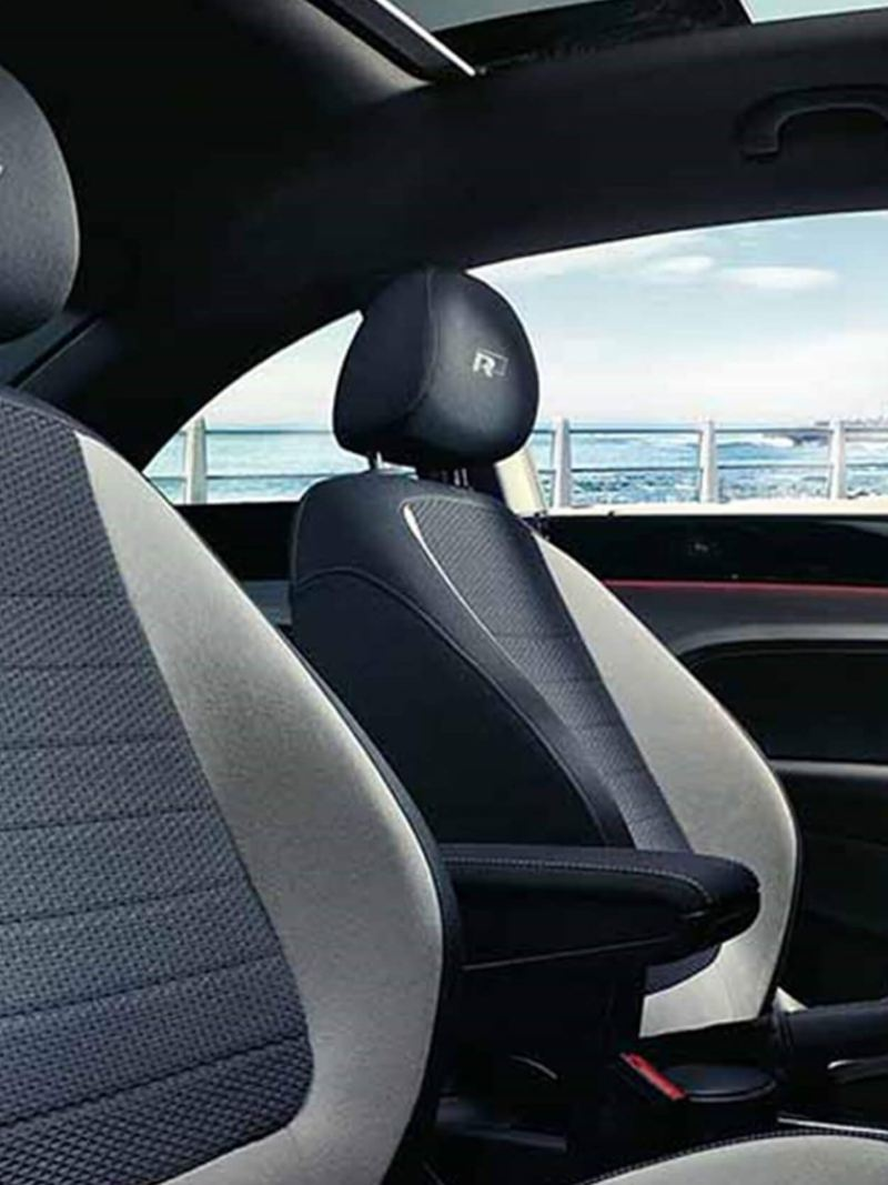 Interior shot of a Volkswagen Beetle, with the sea in the background.