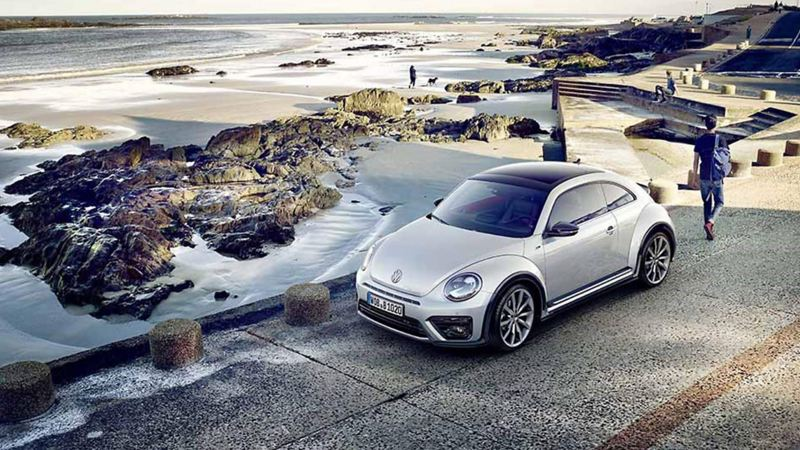 A white Volkswagen Beetle, on a rocky coastal road.