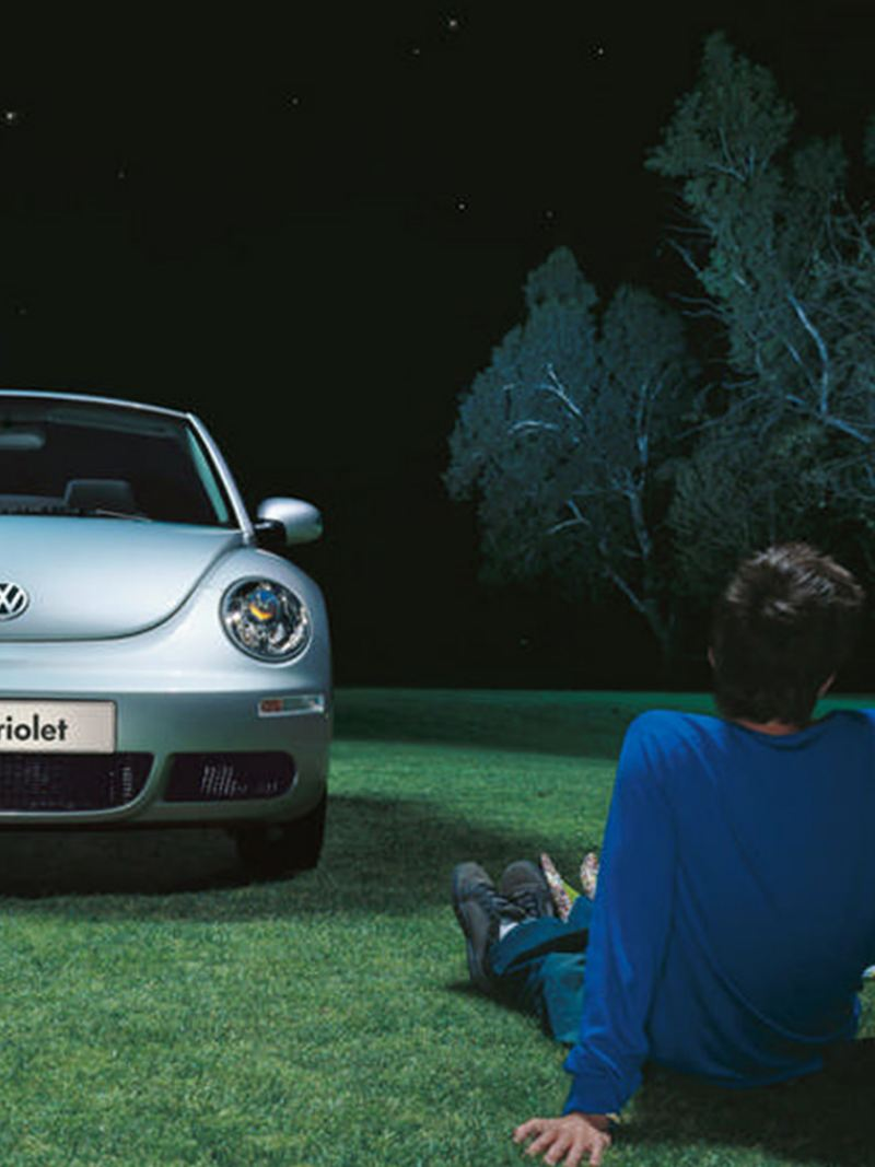 A blue Volkswagen Beetle Cabriolet, in a field with a couple under a tree.