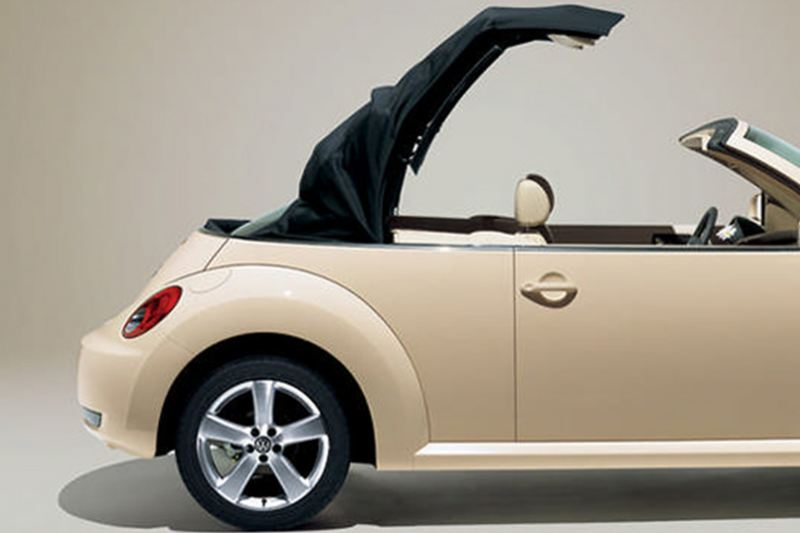 Profile shot of a cream Volkswagen Beetle Cabriolet, the roof opening.