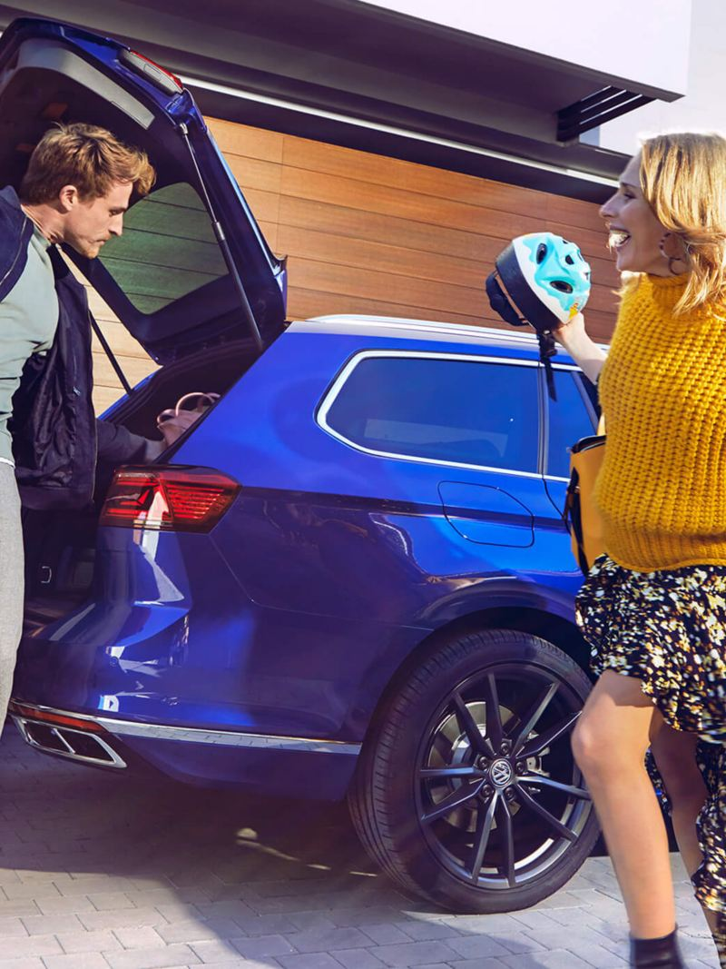 A family getting into a blue Volkswagen Passat Estate, going on a trip.