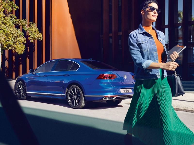A woman walking past a blue Volkswagen Passat Saloon