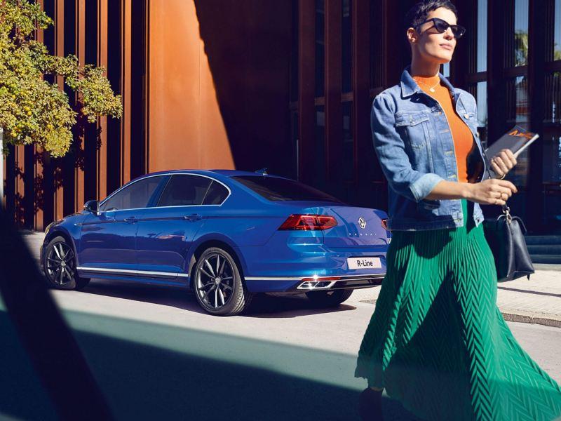 A woman walking past a blue Volkswagen Passat Saloon