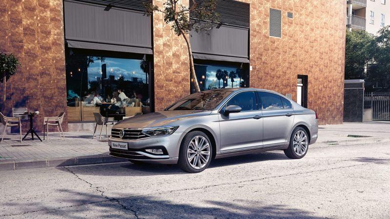 A silver Volkswagen passat parked in front of a restaurant