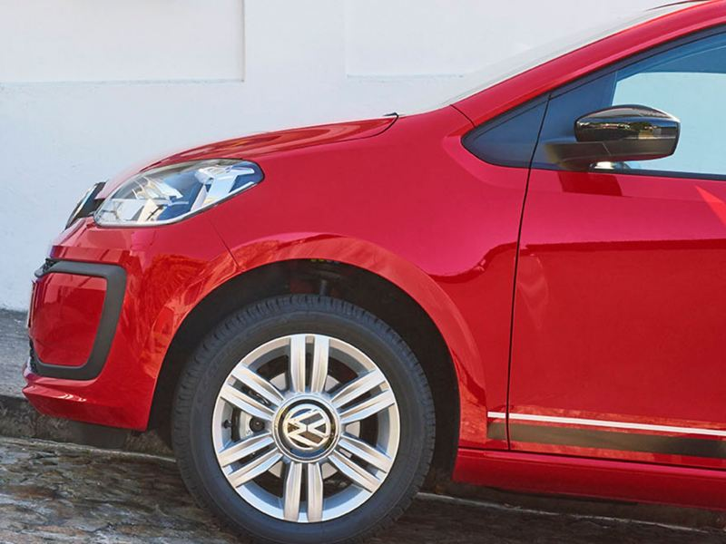 Red Volkswagen up! facing up a steep cobbled street.