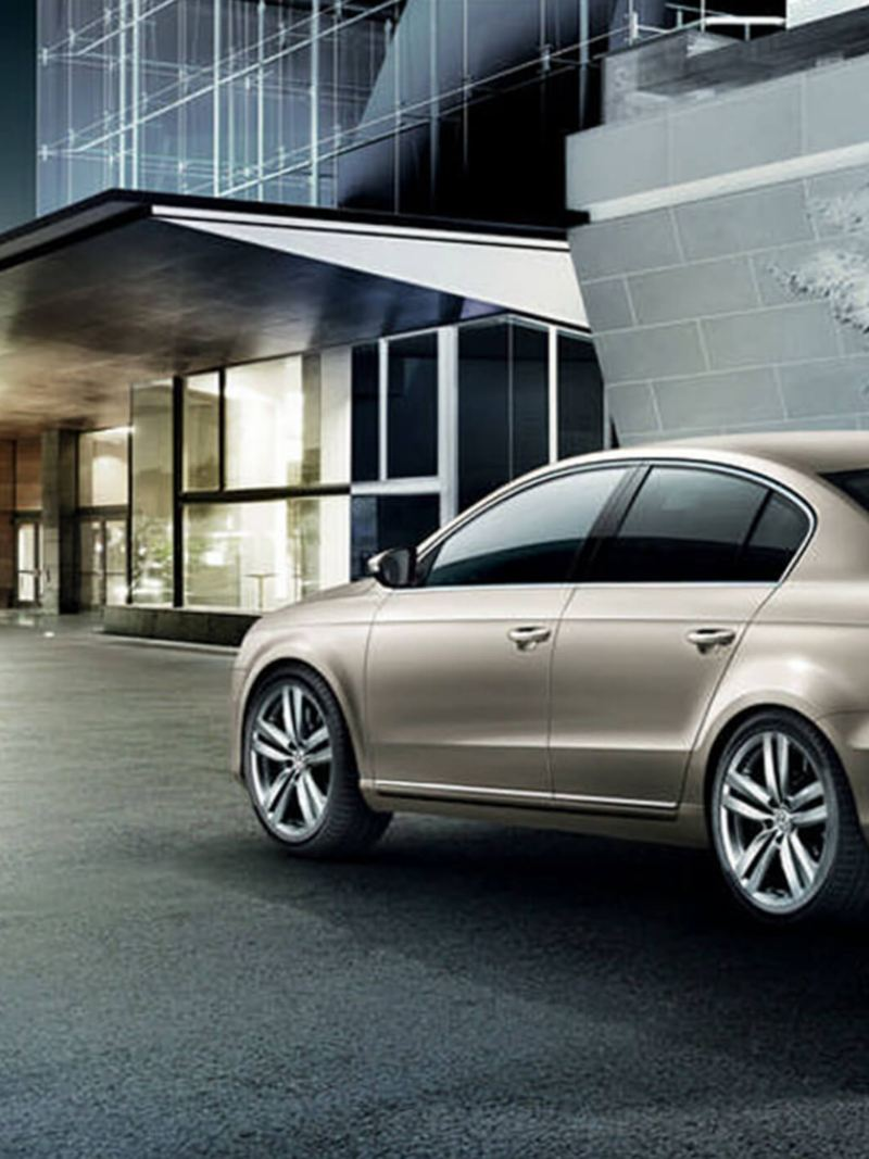 Rear shot of a bronze Volkswagen Passat, outside a glass building at night in the winter.