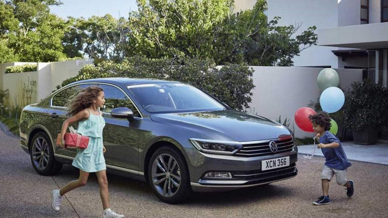 Two children playing around a Volkswagen Passat, outside their family home.