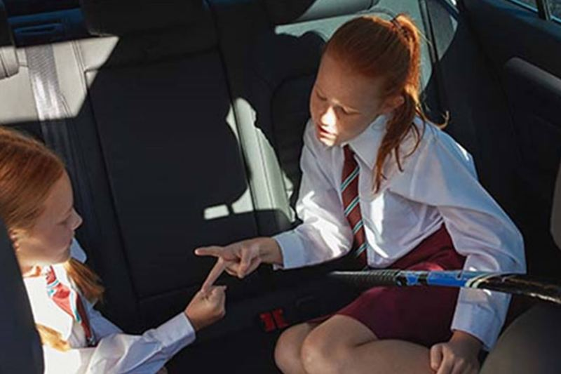 Two school children, playing in the back of a Volkswagen Passat.