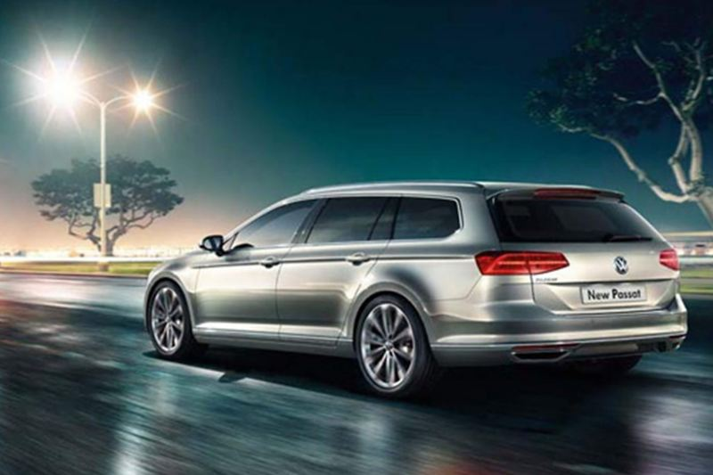 Rear shot of a silver Volkswagen Passat Estate, driving on a wet road.
