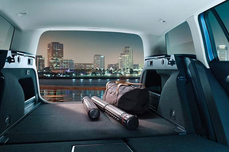 Interior shot of a Volkswagen Passat Estate , seats down, boot open and a night time city skyline in the distance.